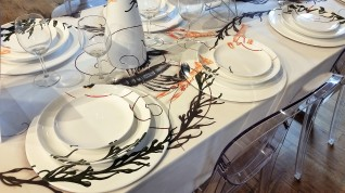 An artist painted this table arrangement for sale in a specialty store. The lobster and algae design is unique insofar as the art delineates the table pieces.
